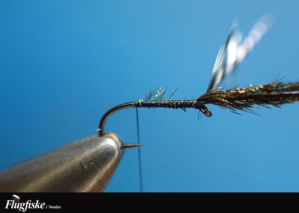 2. Fäst in hacklet och sedan ett påfågelherl, tänk på att fästa in herlet med spetsen framåt för att få en fin tapering på kroppen.