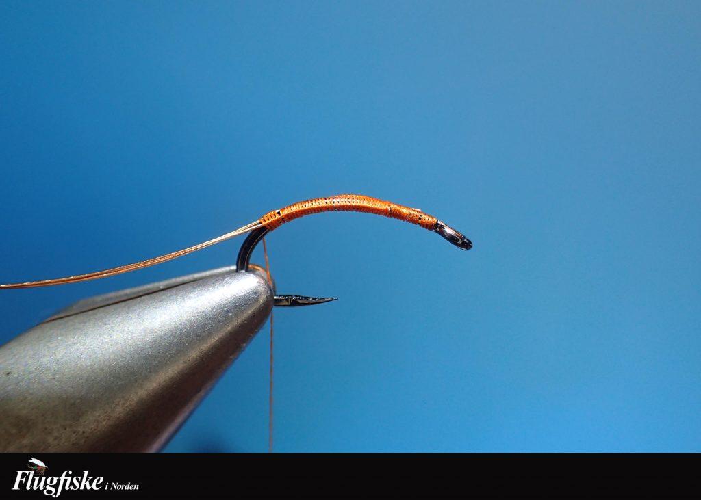 1. Starta med bindtråden bakom krokögat. Lägg en ca dm lång koppartråd dubbel (som en ögla) och bind in denna några mm ner på kroken.Fäst hela vägen ned i böjen som på bild.